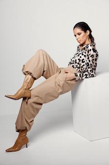 Mujer bonita en ropa de moda posando en botas