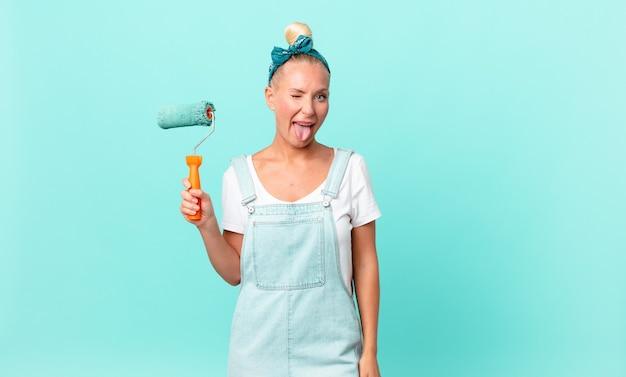Mujer bonita rubia con actitud alegre y rebelde, bromeando y sacando la lengua y pintando una pared
