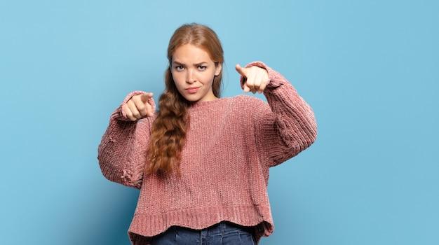 Mujer bonita rubia apuntando hacia la cámara con ambos dedos y expresión enojada, diciéndole que cumpla con su deber