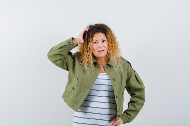 Mujer bonita rubia en chaqueta verde manteniendo la mano en la cabeza y mirando confundido, vista frontal.