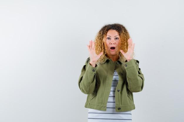 Mujer bonita rubia en chaqueta verde mostrando gesto de rendición y mirando sorprendido, vista frontal.