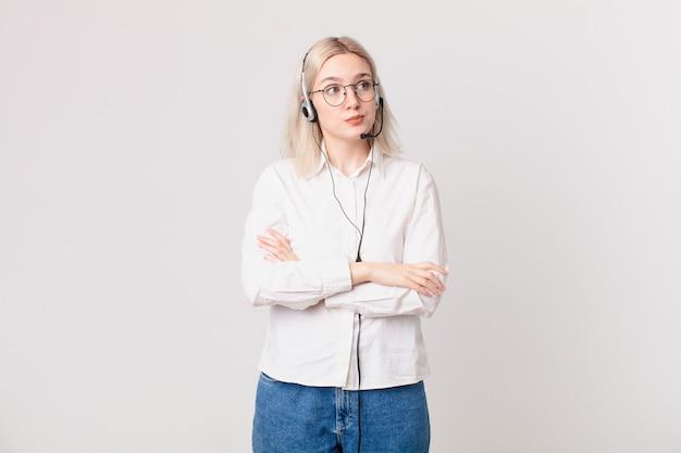 Mujer bonita rubia encogiéndose de hombros, sintiéndose confuso e incierto concepto de telemarketing