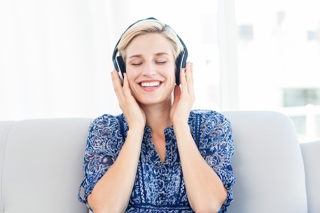 Mujer bonita rubia escuchando música en el sofá