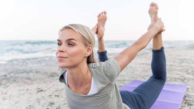 Mujer bonita rubia haciendo yoga en la playa
