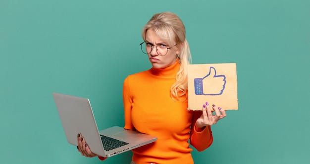 Mujer bonita rubia con un ordenador portátil y como signo de botón