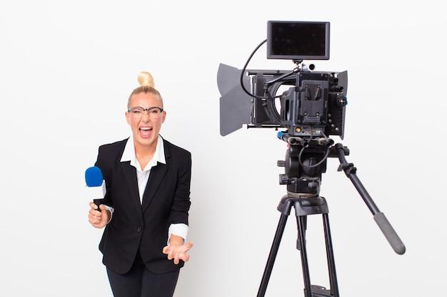 Mujer bonita rubia que parece enojada, molesta y frustrada y que sostiene un micrófono. concepto de presentador