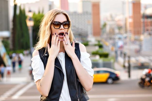 Mujer bonita rubia que se queda en la calle, ve algo y hace una cara sorprendente