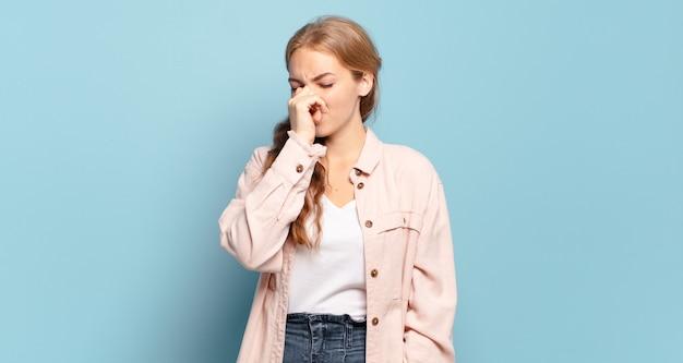 Mujer bonita rubia que se siente disgustada, tapándose la nariz para evitar oler un hedor desagradable y desagradable