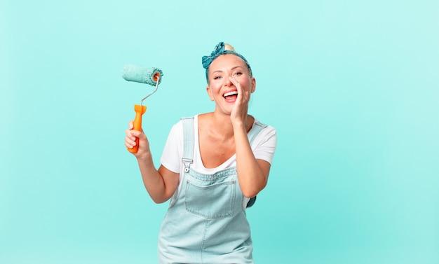 Mujer bonita rubia que se siente feliz, dando un gran grito con las manos al lado de la boca y pintando una pared