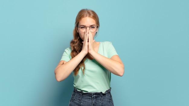 Mujer bonita rubia que se siente preocupada, esperanzada y religiosa, orando fielmente con las palmas presionadas, pidiendo perdón