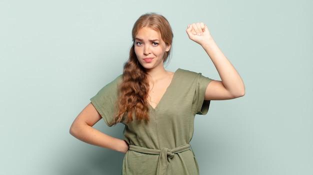 Mujer bonita rubia que se siente seria, fuerte y rebelde, levanta el puño, protesta o lucha por la revolución