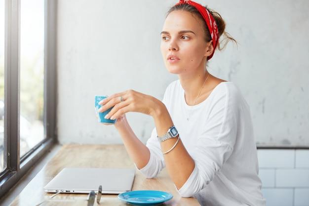 Mujer bonita rubia sentada en el café