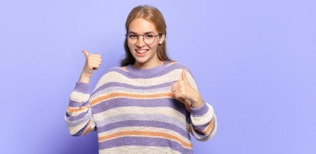 Mujer bonita rubia sonriendo ampliamente mirando feliz, positivo, seguro y exitoso, con ambos pulgares hacia arriba