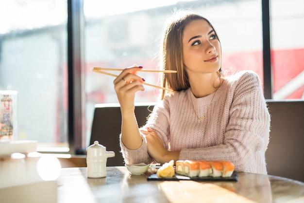 Mujer bonita rubia en suéter blanco comiendo sushi para el almuerzo en una pequeña cafetería
