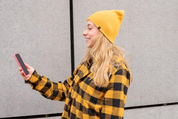 Mujer bonita rubia, vestida con ropa casual, colores amarillos, usando su teléfono inteligente en la calle mientras camina y sonríe