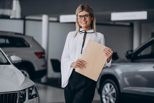 Mujer bonita en una sala de exhibición de autos
