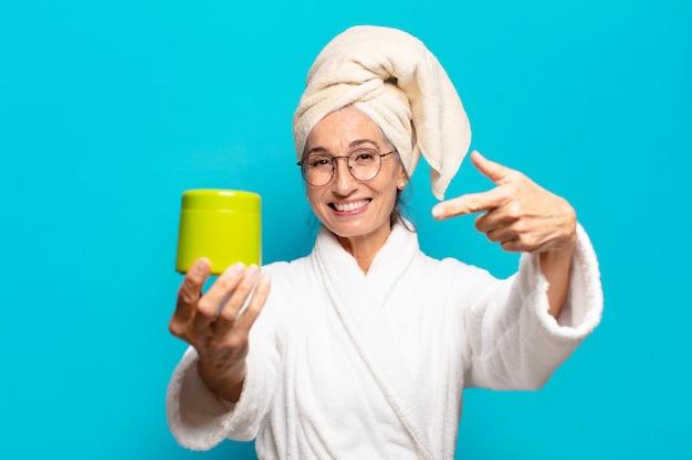 Mujer bonita senior después de la ducha con albornoz. concepto de productos de ducha o limpieza facial