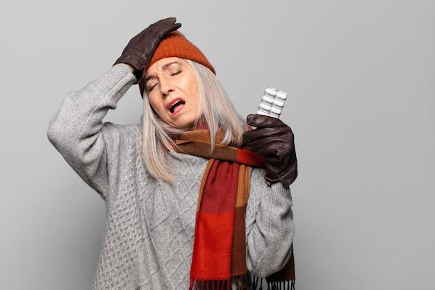 Mujer bonita senior con una tableta de píldoras vistiendo ropa de invierno