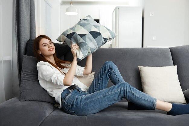 Mujer bonita sentada en el sofá en casa descansando