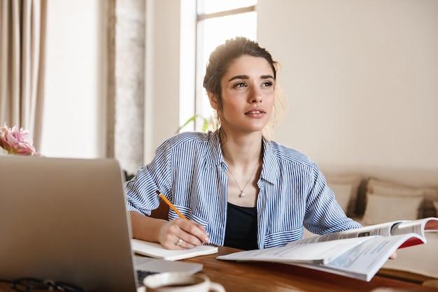 Mujer bonita sincera en ropa casual estudiando con libros de texto y usando la computadora portátil en casa