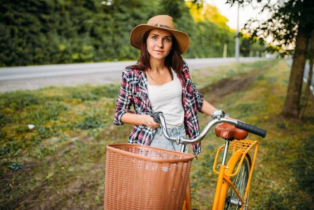 Mujer bonita con sombrero contra bicicleta vintage amarilla con canasta, parque de verano verde. ciclismo al aire libre. chica en ciclo retro