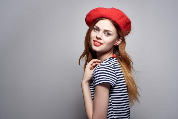 Mujer bonita con un sombrero rojo maquillaje moda francia europa posando fondo claro. foto de alta calidad