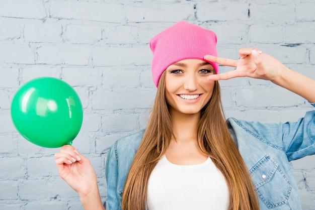 Mujer bonita con sombrero rosa sosteniendo globo y gesticulando con dos dedos cerca de los ojos