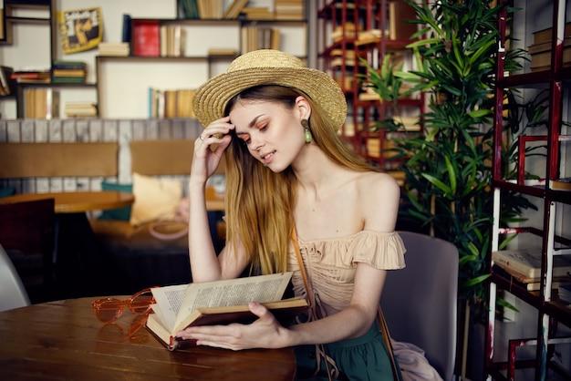 Una mujer bonita con un sombrero se sienta a la mesa con libros en primer plano de fondo.