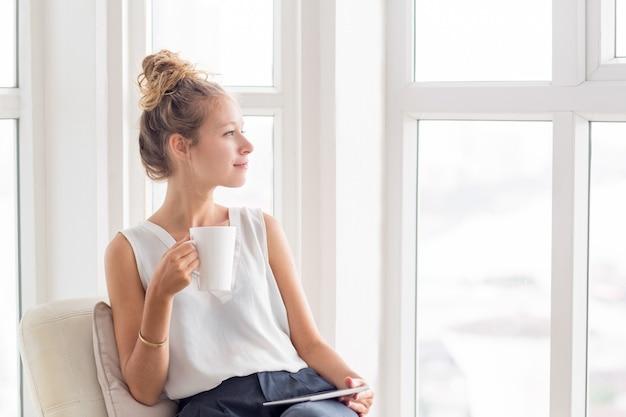 Mujer bonita soñadora con el té y la tableta en loggia