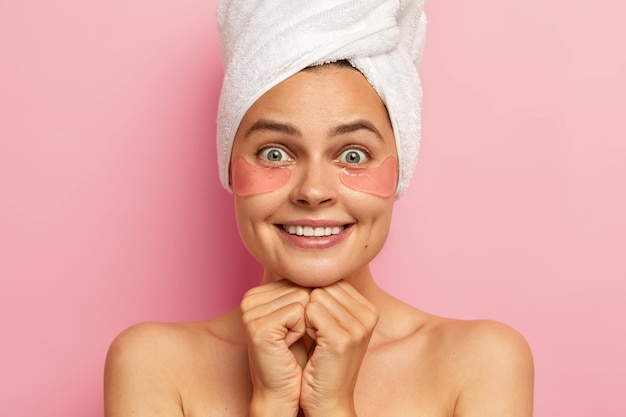 Mujer bonita sonríe agradablemente, muestra dientes blancos, aplica parches debajo de los ojos para reducir las arrugas