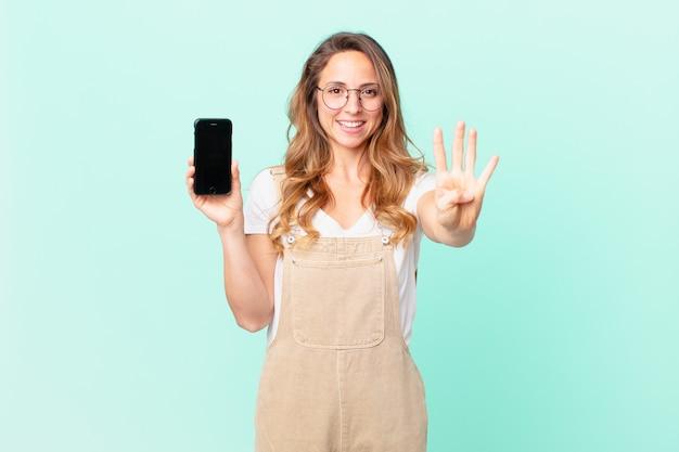 Mujer bonita sonriendo y mirando amigable, mostrando el número cuatro y sosteniendo un teléfono inteligente