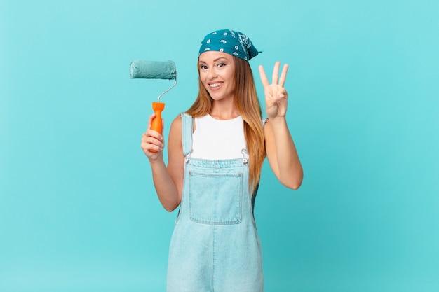 Mujer bonita sonriendo y mirando amigable, mostrando el número tres pintando una nueva pared de casa