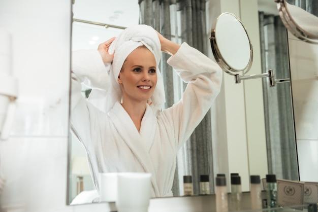 Mujer bonita sonriente en bata de baño
