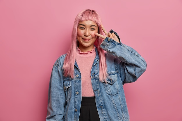 Una mujer bonita sonriente desea suerte y paz, muestra el signo de la victoria, hace una linda cara seductora, se divierte, tiene el pelo largo y liso teñido de rosa, usa una chaqueta de jean