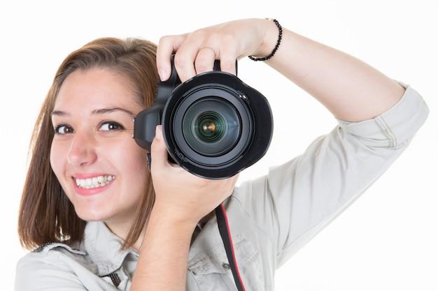 Mujer bonita sonriente del fotógrafo de la chica joven en blanco