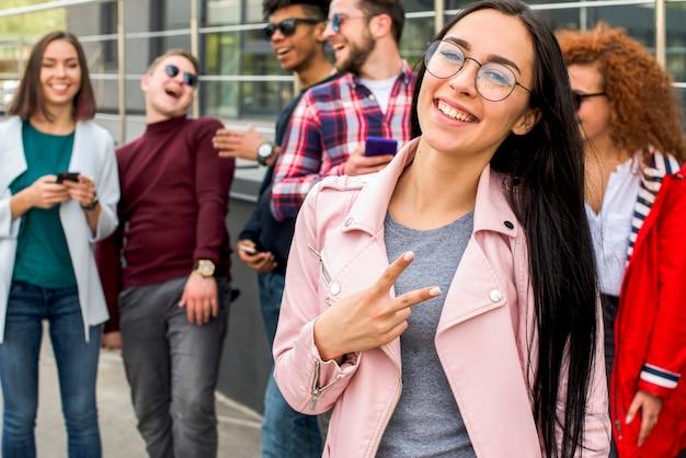 Mujer bonita sonriente que se coloca delante de sus amigos que gesticulan la muestra de la victoria