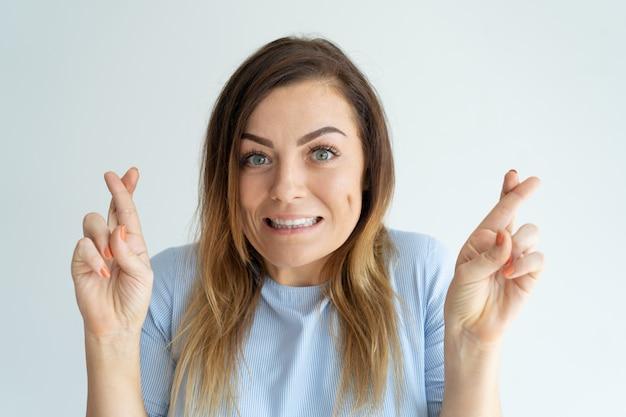 Mujer bonita sonriente que muestra gesto cruzado de los dedos. lady haciendo un deseo.