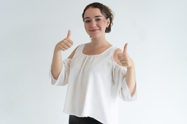 Mujer bonita sonriente que muestra los pulgares para arriba