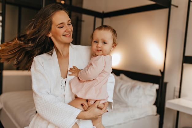 Mujer bonita con sonrisa mira a su bebé. mamá en bata de baño girando con el bebé en brazos en el dormitorio.