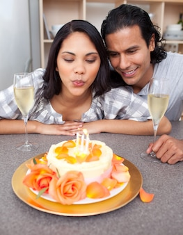 Mujer bonita soplando velas con su esposo por su cumpleaños