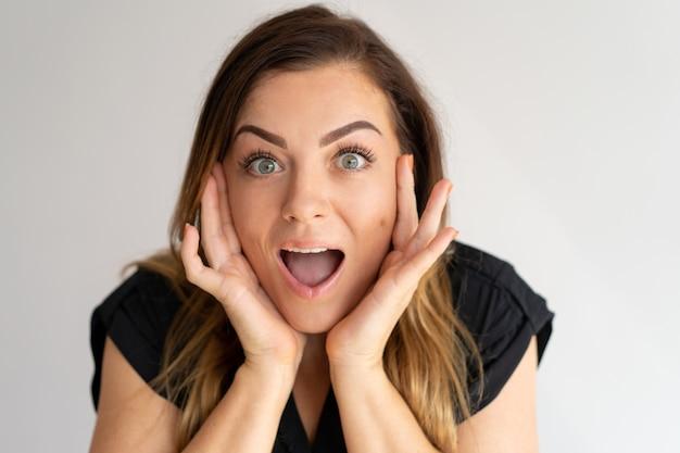 Mujer bonita sorprendida que toca la cara con su boca abierta