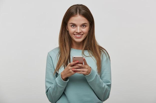 Mujer bonita sosteniendo teléfono móvil y escuchando música