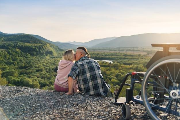 Una mujer bonita y su esposo incapacitado se sientan cerca de su silla de ruedas en la colina y se besan suavemente.