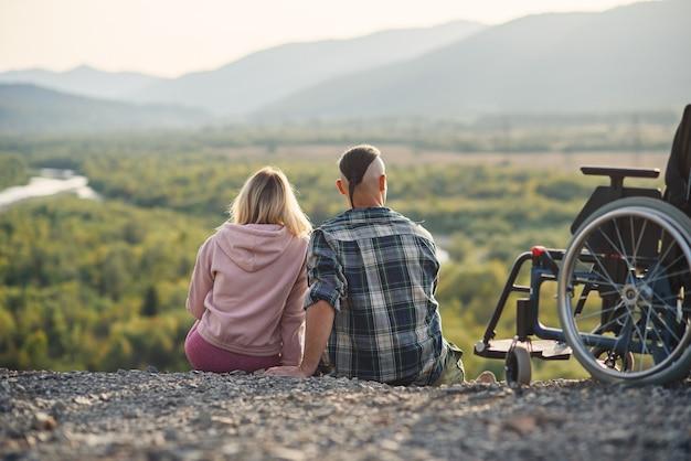 Mujer bonita y su marido incapacitado descansando juntos cerca de su silla de ruedas en la colina.