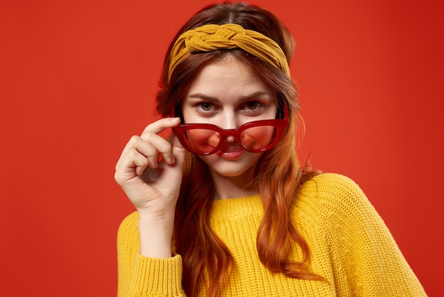 Mujer bonita en suéter amarillo gafas rojas ropa de moda pared roja cerca.