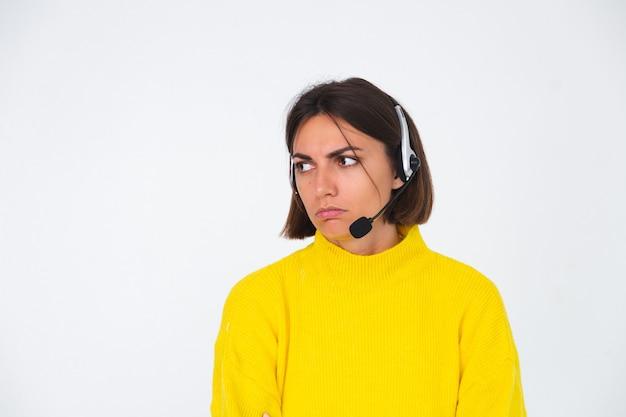 Mujer bonita en suéter amarillo en gerente blanco con auriculares infeliz cansado aburrido