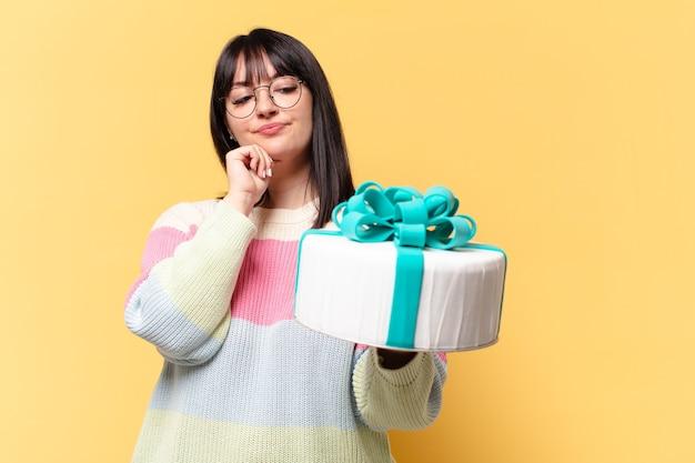 Mujer bonita de talla grande con un pastel de cumpleaños