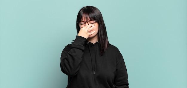 Mujer bonita de talla grande que se siente disgustada, tapándose la nariz para evitar oler un hedor desagradable y desagradable