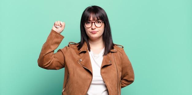 Mujer bonita de talla grande que se siente seria, fuerte y rebelde, levanta el puño, protesta o lucha por la revolución