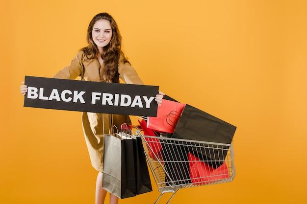 Mujer bonita tiene cartel de viernes negro con carrito lleno de bolsas de compras y cinta de señal aislada sobre amarillo